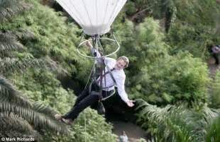 Eden Project trees get trimmed by man hanging from a